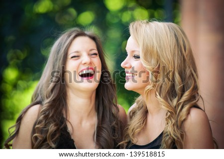 Two beautiful girls laughing together outdoors in a park.