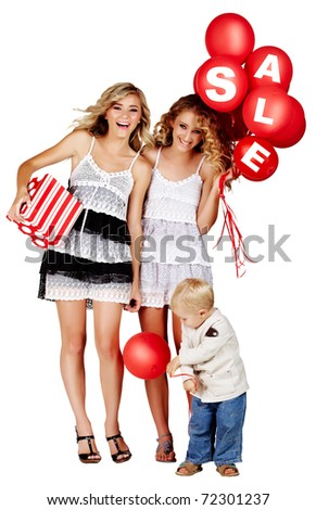 two beautiful girls laughing with red balloons with sign sale and gift box and little boy playing next to them. - stock photo