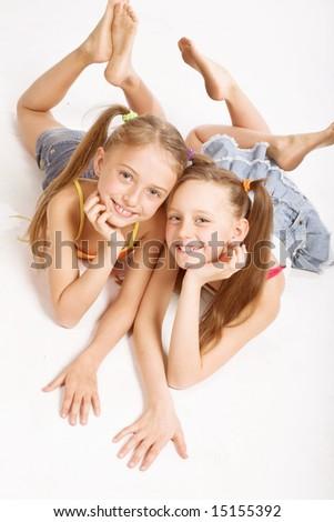 Two beautiful girls  laying on white - stock photo