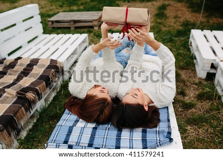 Two beautiful girls lie on the bench and unpacks a gift