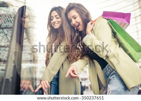 Two beautiful girls making shopping in the city center. Indicating clothes in a shop window - stock photo