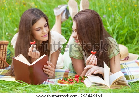 Two beautiful girls on picnic eating strawberry while reading books - stock photo