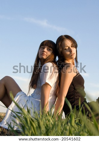 Two beautiful girls on the green grass - stock photo