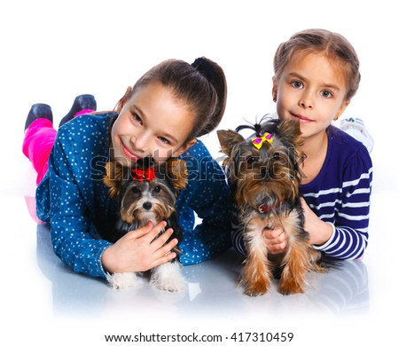 Two beautiful girls playing with her yorkshire terriers. Isolated on the white background - stock photo
