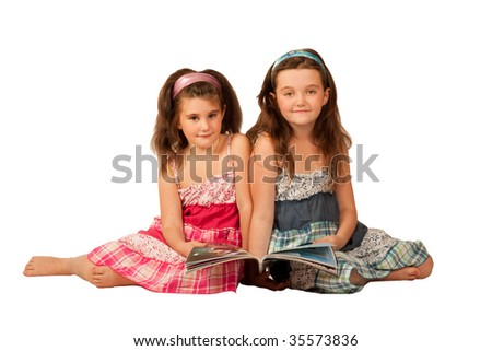Two beautiful girls reading a fashion magazine - stock photo