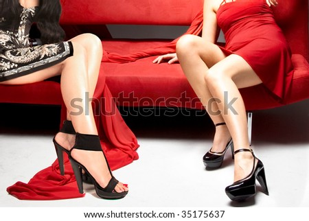 Two beautiful girls sitting on red sofa