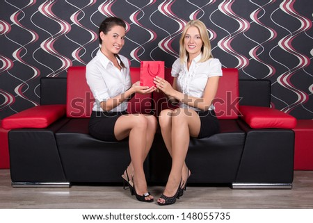 two beautiful girls sitting on the sofa with present bag - stock photo