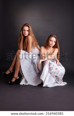 Two beautiful girls twins, isolated on the black background - stock photo