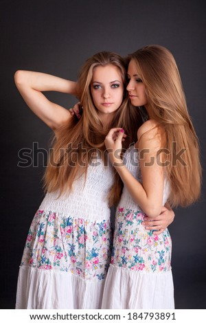 Two beautiful girls twins on the black background - stock photo