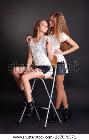 Two beautiful girls twins, on the black background - stock photo