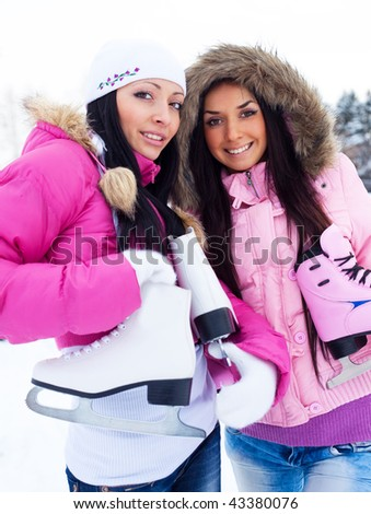 two beautiful girls wearing warm winter clothes going to  ice skate - stock photo