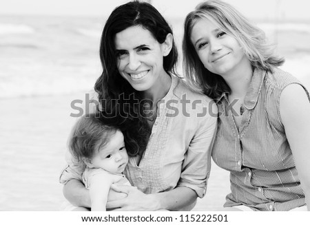 two beautiful girls with a baby on the beach - stock photo
