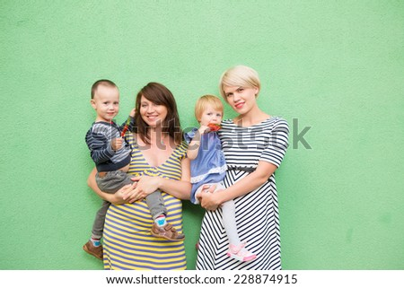 two beautiful girls with a children on the green background  - stock photo