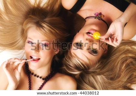 Two beautiful girls with bright makeup licking lollipops - stock photo