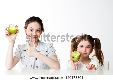 two beautiful girls with green apples - stock photo