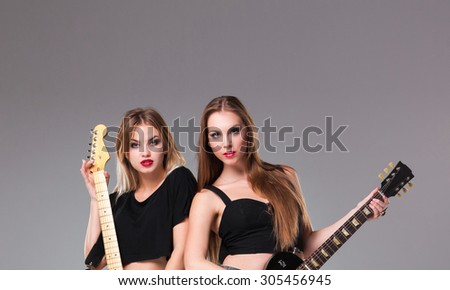 Two beautiful girls  with long hair playing guitars in rock style on a gray background - stock photo