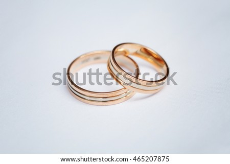 Two beautiful golden wedding rings on white background, close up
