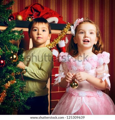 two beautiful happy child decorate christmas tree - stock photo