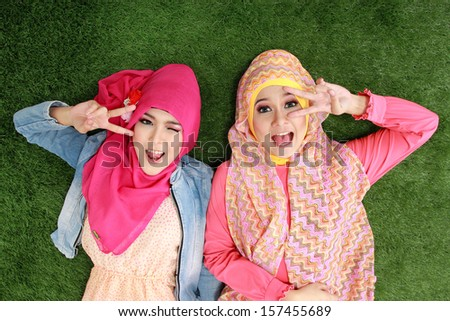 two beautiful happy muslim woman smiling lying on grass - stock photo