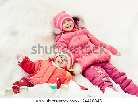 Two beautiful happy sisters lying in the snow winter outdoors.