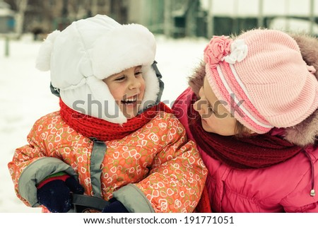 Two beautiful happy sisters winter outdoors.