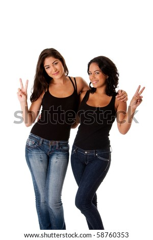 Two beautiful happy smiling young women couple friends making peace victory gesture with fingers while hugging each other, wearing black tank top and blue denim jeans, isolated. - stock photo