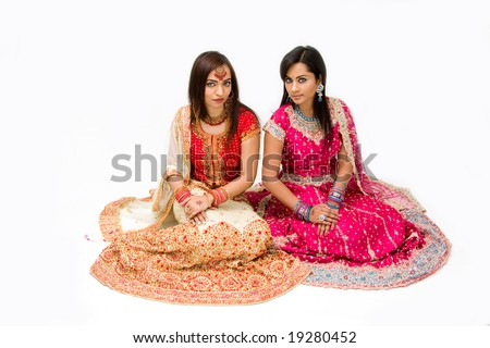 Two beautiful harem girls or belly dancers or Hindu brides sitting, isolated - stock photo