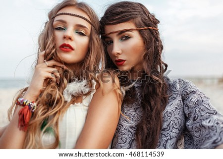 Two beautiful hippie girls with bright make up and hairstyle looking at camera