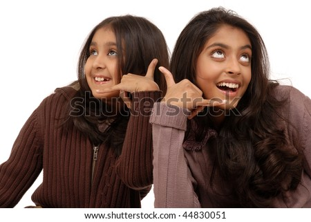 two beautiful indian girls showing the call sign isolated on white background - stock photo