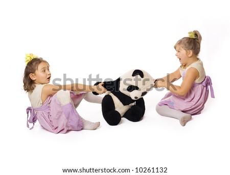 Two beautiful kids struggle for panda over white - stock photo