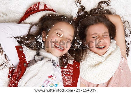 Two beautiful little girl with long hair in a white winter sweater lying in the snow under the Christmas tree and laugh gift for New Year Merry Christmas card - stock photo