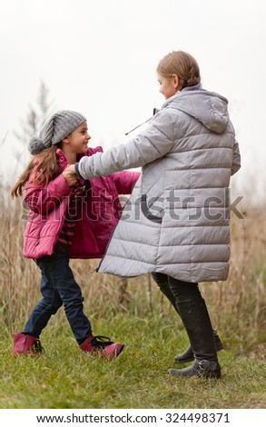 Two beautiful little girls dancing outdoors in  autumn day - stock photo