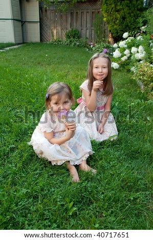 Two beautiful little girls  enjoy summer on backyard - stock photo