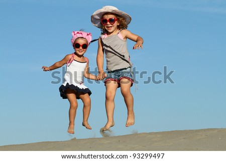 Two beautiful little girls jumping on the sand - stock photo