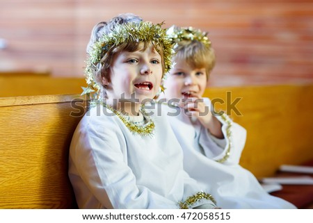 Two beautiful little kids in angel clothes for Christmas story in a church. Happy adorable blond children, boys singing and excited about holiday.