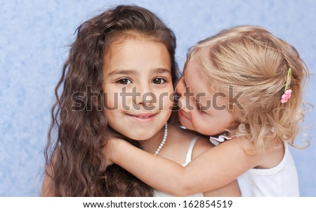 Two beautiful little sisters hugging on a white background