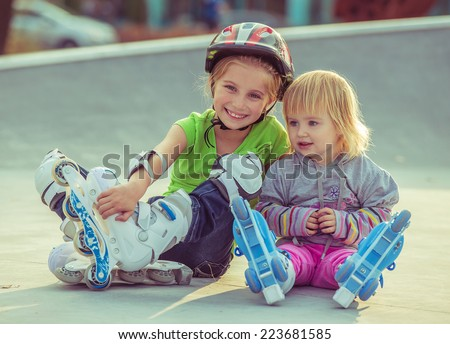 two beautiful little sisters in a roller skates sitting  on the street - stock photo
