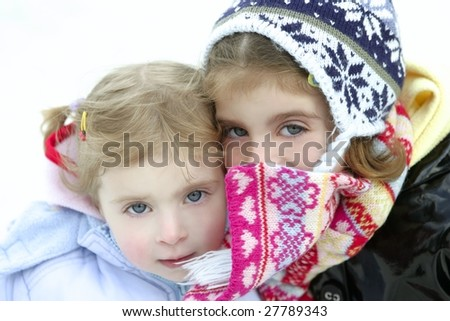 Two beautiful little sisters on the snow with winter wool hat