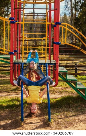 Two beautiful little sisters playing on the playground in a summer park. - stock photo