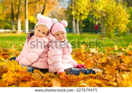 Two beautiful little sisters sitting on yellow leaves in the autumn park and smiling
