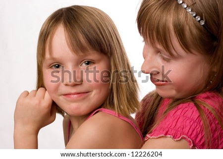 Two beautiful little smiling girls looking sisters isolated on white background - stock photo