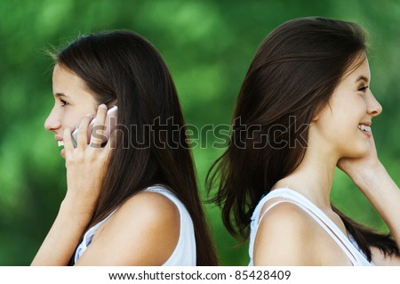 two beautiful long-haired woman profile standing behind each talk phone - stock photo