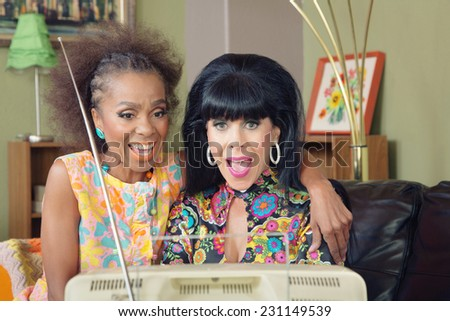 Two beautiful mature woman watching television together - stock photo
