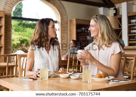 stock photo two beautiful mature women holding cup of coffee and talking to each other in a cafeteria senior 705175744