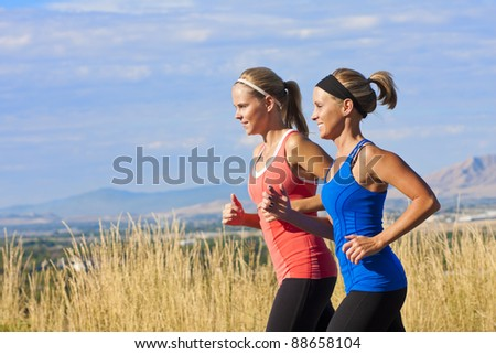 Two beautiful middle-aged female joggers training for a marathon - stock photo