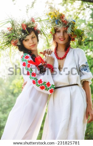 Two beautiful models in national costumes - stock photo