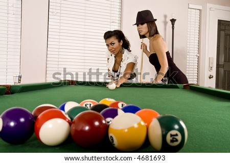 Two beautiful models play pool / billiards