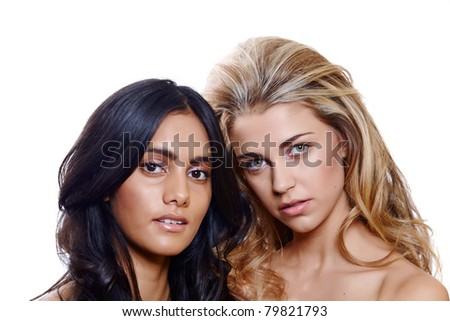 two beautiful models with blond and brown long curly hair on white background. Focus on the blond woman