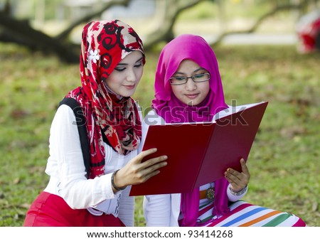 Two beautiful Muslim woman being reading book in action. - stock photo
