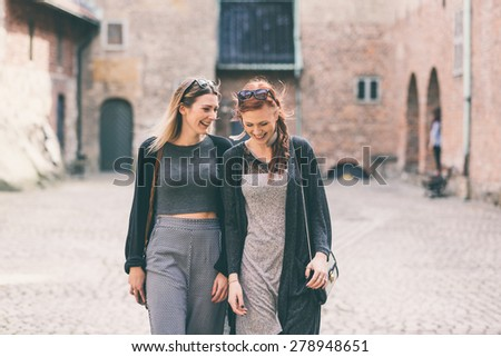 Two beautiful nordic girls  visiting old fortress in Oslo, talking and laughing. Lifestyle, tourism and friendship concepts. - stock photo